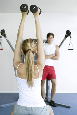 Woman lifting dumbbells with a man watching her in the background photo