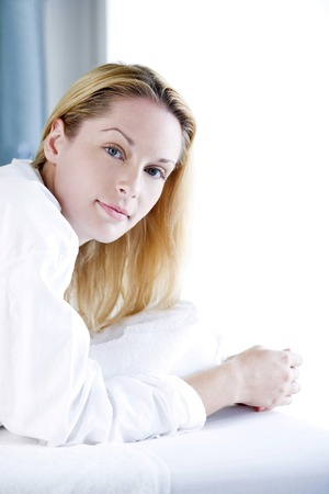 lying forward: Woman lying forward on massage table, looking at the camera