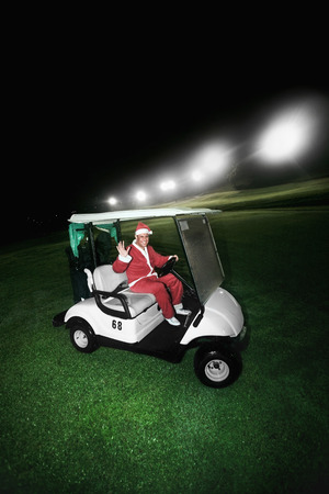 Man in Santa suit driving a golf cart photo