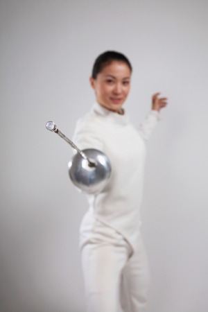 quarter foil: Woman in fencing suit posing for the camera Stock Photo