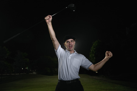 Man holding golf club cheering at golf course photo