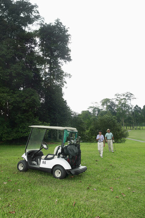 Two men walking towards golf cart photo