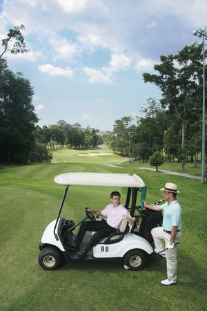 Man in golf cart talking to his friend photo