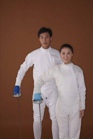 quarter foil: Man and woman in fencing suits posing for the camera
