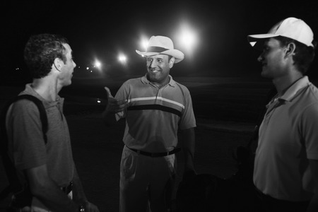 Three men on golf course at night photo