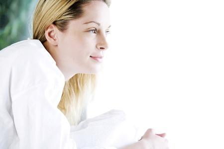 lying forward: Woman lying forward on massage table, looking away