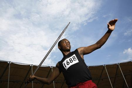 Man throwing javelin in stadium