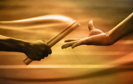 Dwóch mężczyzn przechodzących złotą pałeczkę na stadionie