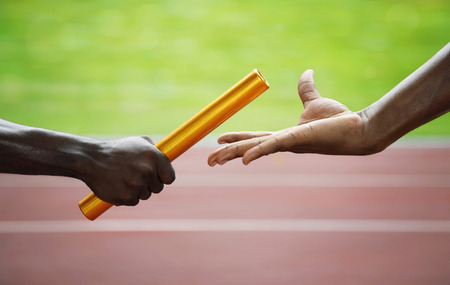 Two men passing golden baton in stadium Stock Photo