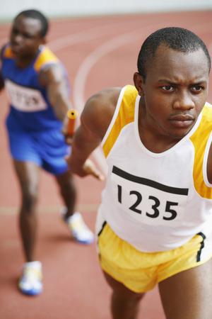 Men passing baton in relay race photo