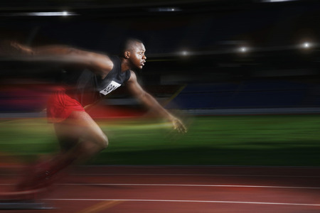 Man running at a fast speed on the running track Stock Photo