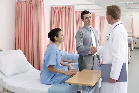 Man shaking doctors hand, woman watching photo