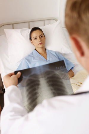 Doctor looking at X-ray image, patient lying on the bed photo