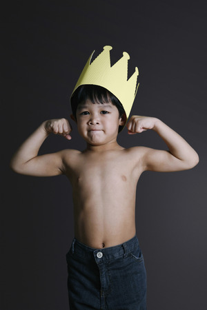 Boy flexing his muscles photo