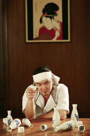 Man with his eyes half closed after a few cups of sake photo