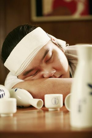 Man asleep on the table after a few cups of sake photo