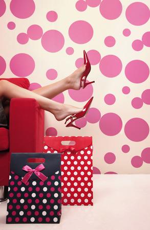 allurement: Womans legs on the sofas arm rest Stock Photo