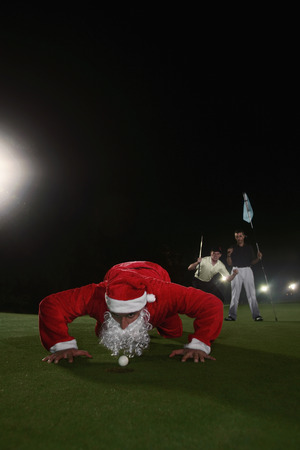 Man in Santa suit blowing golf ball into hole with two men cheering in the background photo