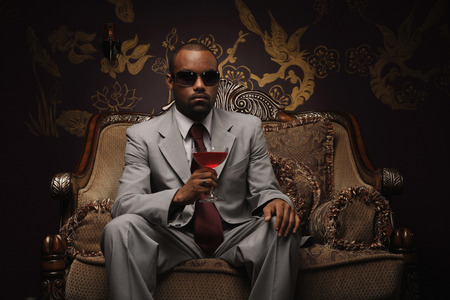 Businessman with sunglasses holding a glass of cocktail photo