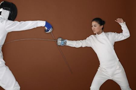 fencing foil: Woman with fencing foil attacking her opponent Stock Photo