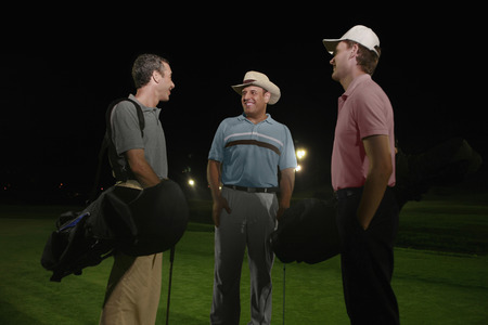 Three men on golf course at night photo