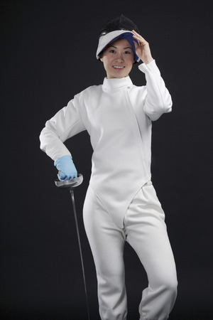 fencing foil: Woman with fencing foil posing for the camera
