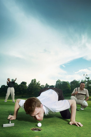 blow hole: Man trying to blow golf ball into the hole with friends watching in the background Stock Photo
