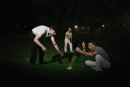 Three men searching for missing golf ball photo