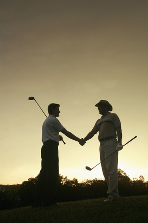 Two men with golf clubs shaking hands photo