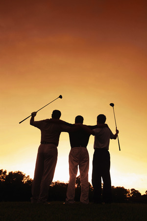 man rear view: Three men at golf course during sunset Stock Photo