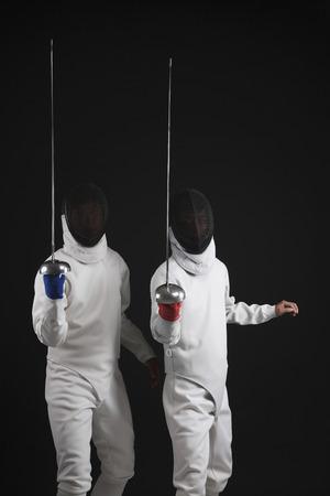 quarter foil: Two men holding fencing foils Stock Photo