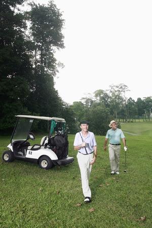 Two men walking by a golf cart photo