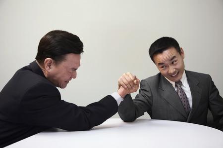 frowns: Businessmen arm wrestling Stock Photo