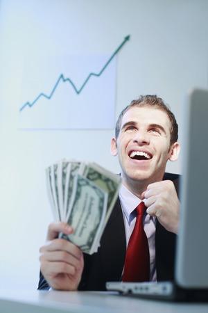 jubilating: Businessman smiling while holding banknotes Stock Photo