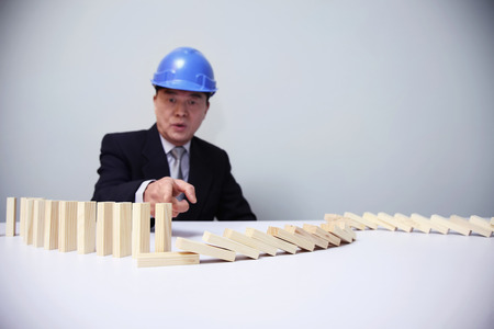 Businessman with safety helmet pointing at wooden blocks on the table photo