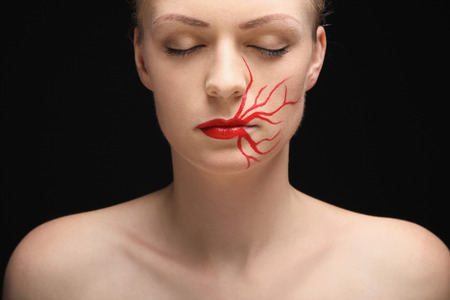 closes eyes: Woman with lipstick drawing on her face closing her eyes Stock Photo