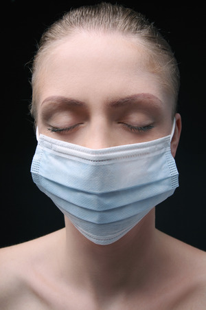 eyes closing: Woman with surgical mask closing her eyes Stock Photo