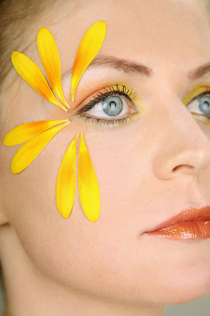 contemplates: Woman with flower petals decorating her face Stock Photo