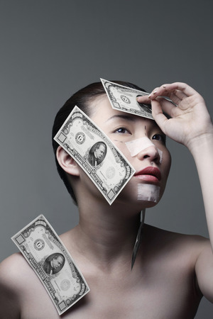 cosmetic surgery: Woman with cosmetic surgery markings and banknotes sticking her face and shoulder