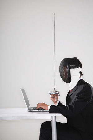 fencing foil: Businessman with a fencing foil and fencing mask using a laptop Stock Photo