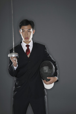 fencing foil: Businessman with a fencing foil and mask Stock Photo
