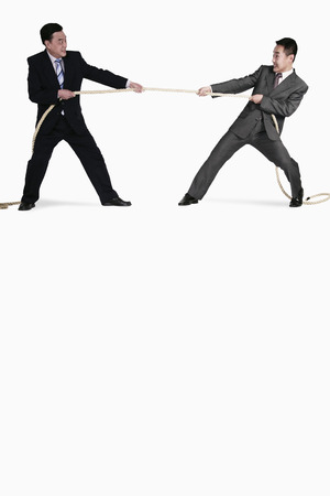 frowns: Businessmen playing tug of war Stock Photo