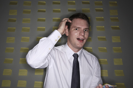 Man scratching his head while holding pen and notepad photo