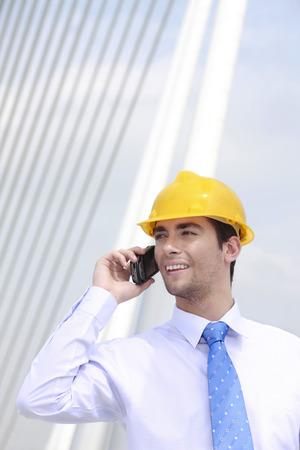 safety helmet: Hombre de negocios con casco de seguridad hablando por tel�fono Foto de archivo