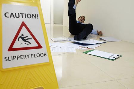 Biznesmen poÅ›lizgu obok znak ostrzegawczy