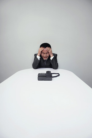 frowns: Stressed businessman waiting for a telephone call