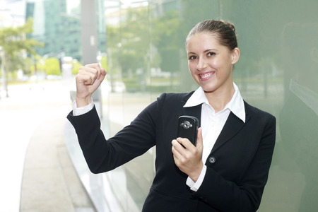 Businesswoman holding cell phone, shaking fist in victory photo