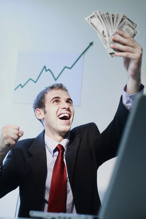 jubilate: Businessman laughing while looking at banknotes