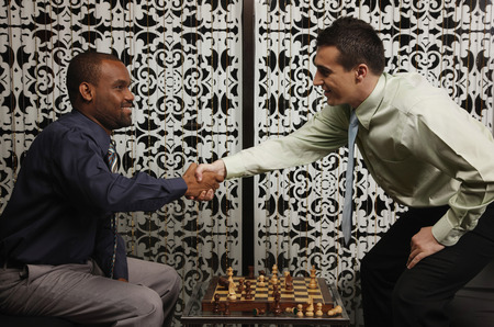 Businessmen shaking hands over chessboard photo