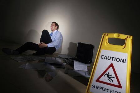 Businessman slipped beside Caution sign, holding onto his leg photo